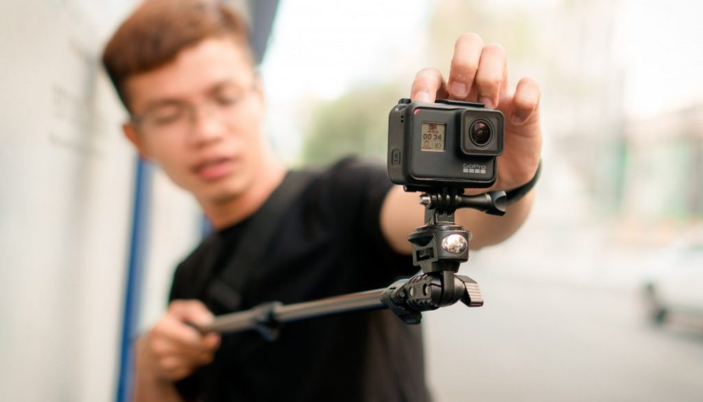 man-holding-monopod-with-action-camera-3055027