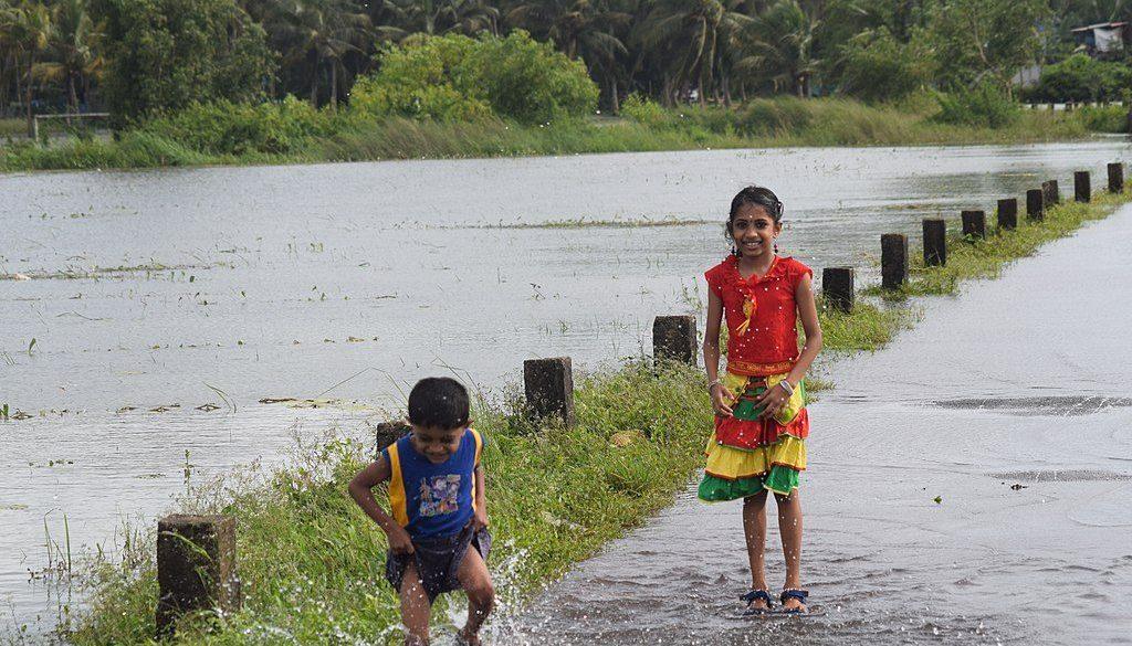 1024px-Children_Playing_in_Rain
