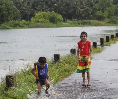 1024px-Children_Playing_in_Rain